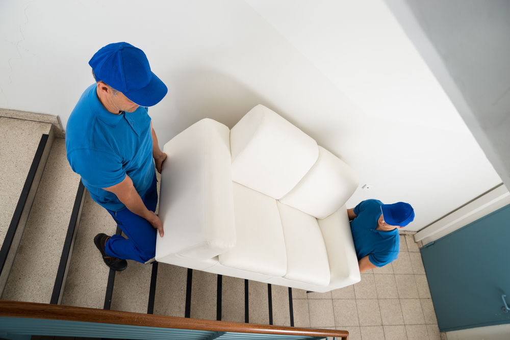 Movers carrying couch down stairs
