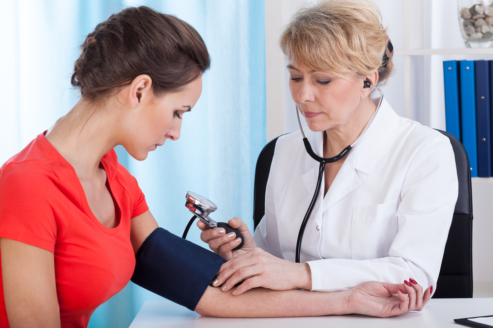Family doctor checking patient's blood pressure